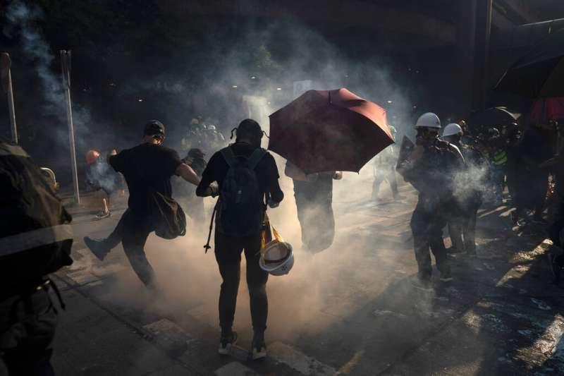 催淚彈引發的煙霧繚繞,以及反送中抗議者戴著防毒面具衝鋒陷陣的場景,已經是香港街頭這三個多月來的日常。(美聯社)