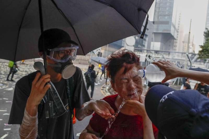 一名沒有裝戴防毒面具的婦人因為香港警察發射的催淚瓦斯涕淚縱橫,其他人趕緊用清水幫她沖洗眼睛與臉部。(美聯社)