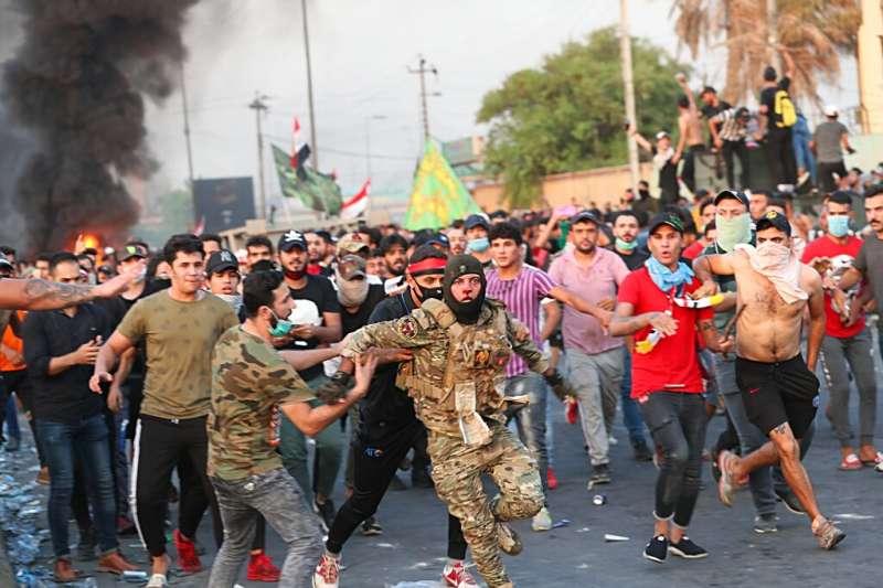 伊拉克10月1日以來爆發全國性反政府示威,成千上萬年輕人自發性走上街頭。圖為一位落單士兵受到大批示威者追打,一名示威者試圖救士兵、拉開士兵與人群的距離。(AP)
