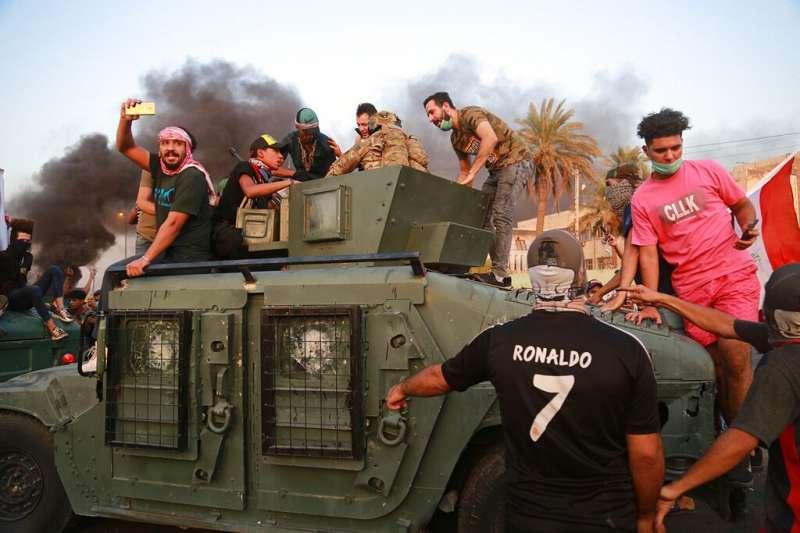 伊拉克10月1日以來爆發全國性反政府示威,成千上萬年輕人自發性走上街頭。圖為示威者爬上官兵的裝甲車上談判。(AP)