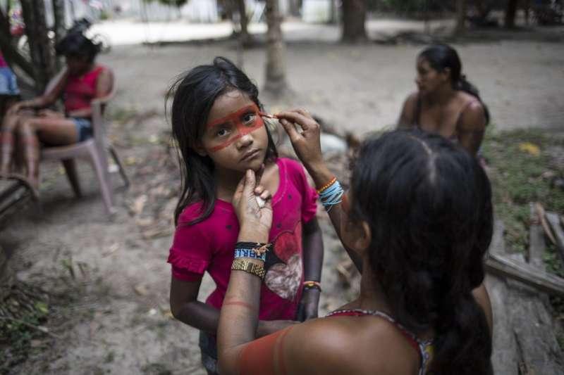 儘管聚落外的影視文化以藉助科技產品傳入村落,但族人仍舊維持臉部彩繪的傳統。(美聯社)