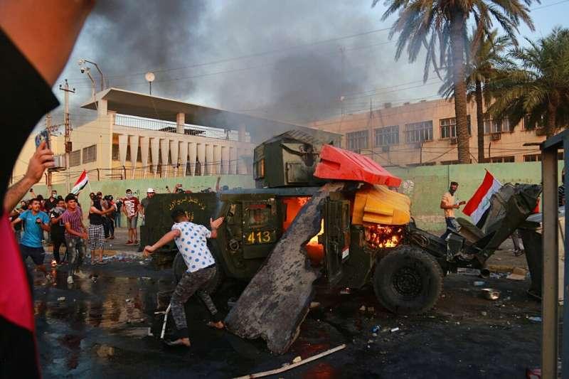 伊拉克10月1日起爆發大規模反政府示威,抗議者放火焚燒一輛軍車。(美聯社)
