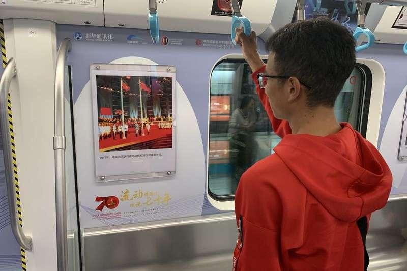 乘客在觀看「成都地鐵流動博物館」裡的照片(新華社)