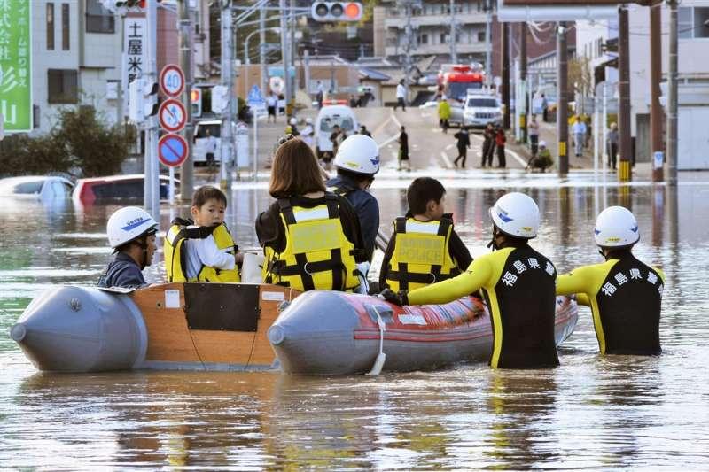 颱風哈吉貝侵襲日本部分地區,救難人員協助救出因淹水受困的民眾。(圖/共同社)