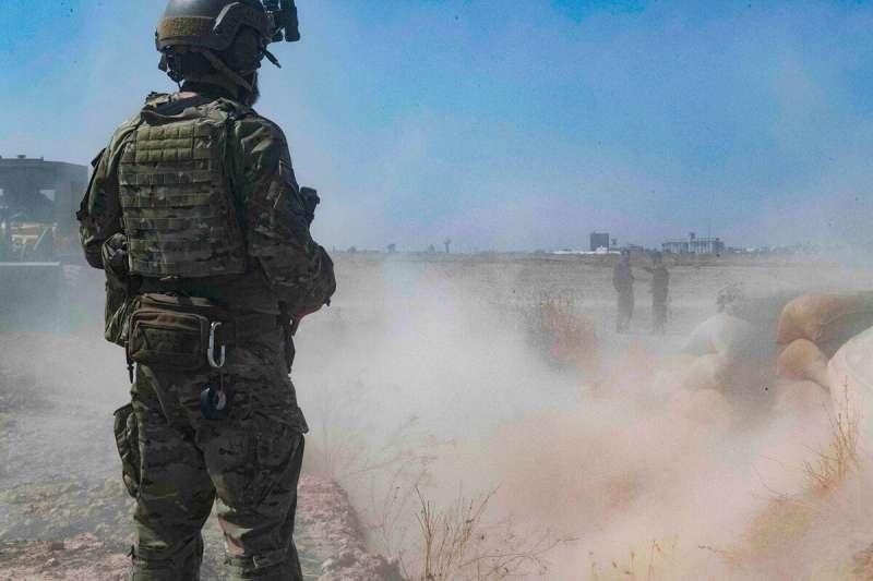 一名美軍望著敘利亞民主軍的庫德族士兵豎立旗幟。美軍面對川普撤軍命令,十分不願拋下共同作戰多年的夥伴。(AP)