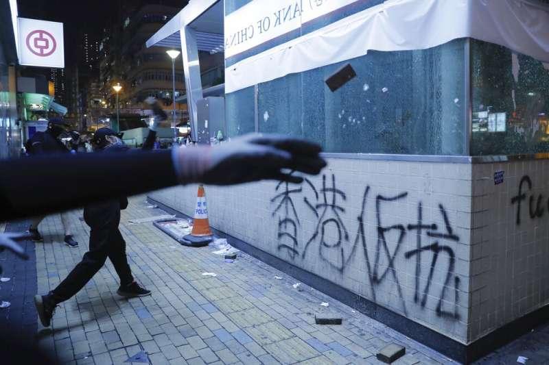 香港的「反送中」抗爭者正在破壞地鐵站入口。(美聯社)