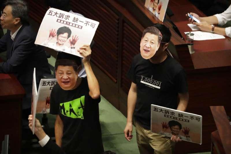 香港泛民主派議員在立法會議場戴起習近平面具,拿著林鄭月娥的看板表達不滿。(美聯社)