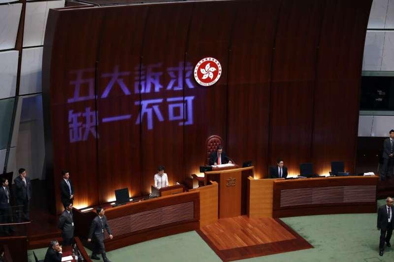 香港特首林鄭月娥16日到立法會進行施政報告,但泛民派議員不斷抗議干擾,還在牆上打出「五大訴求、缺一不可」。(美聯社)