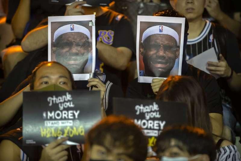 抗議民眾舉著詹姆斯哭臉照片,下方則是感謝莫雷發言力挺。(美聯社)