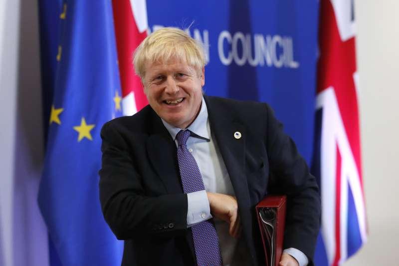 英國首相強森終於與歐盟達成新版退出協議,只待國會表決同意。圖為強森忍不住笑意。(AP)
