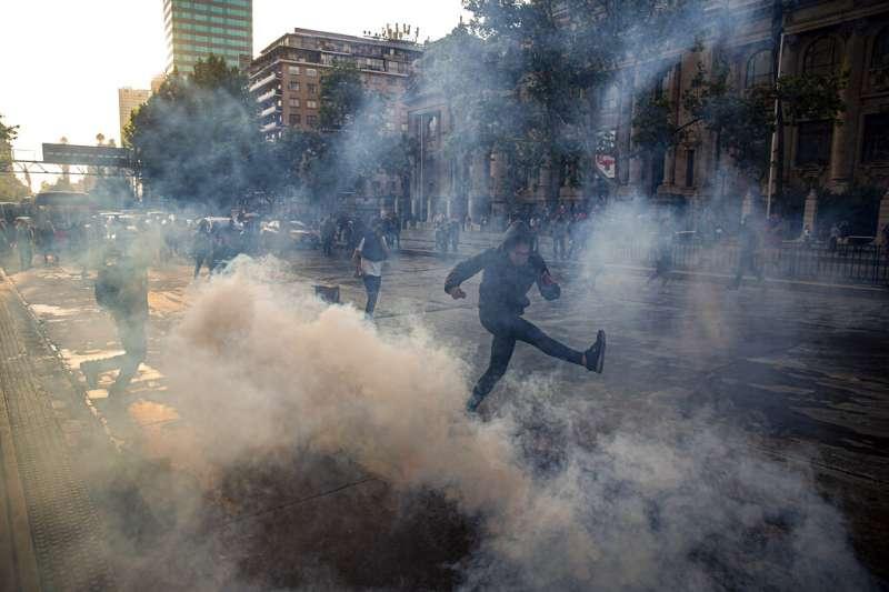 18日下午,智利警方在智利街頭投擲催淚彈,試圖驅離示威群眾。(AP)