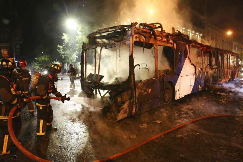 18日晚間,示威者焚燒聖地牙哥市內公車與多處公共設施。(AP)