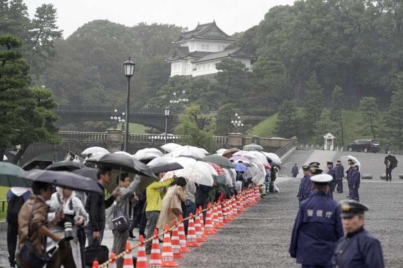 雖然無法進到松之間觀禮,許多日本民眾22日還是冒雨趕到皇居。(美聯社)