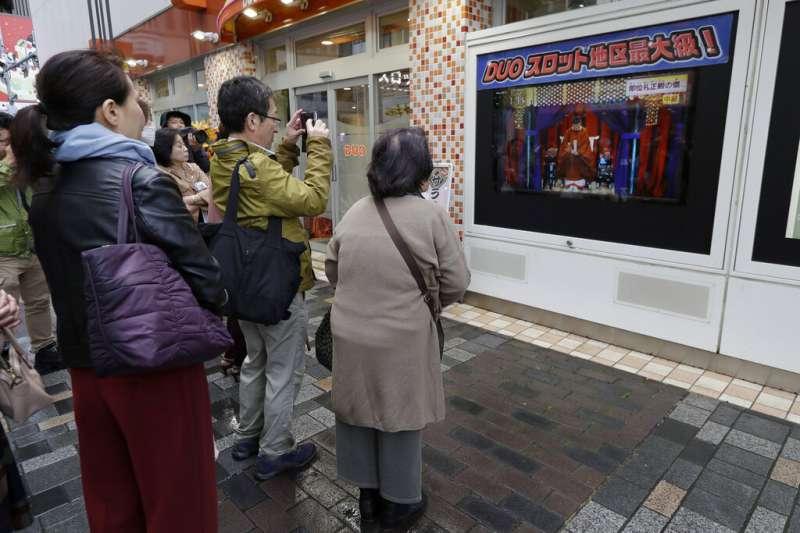 在東京街頭觀看「即位禮正殿之儀」的日本民眾。(美聯社)