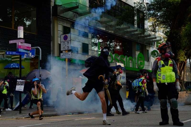 香港反送中抗爭者將催淚彈丟還警方。(美聯社)