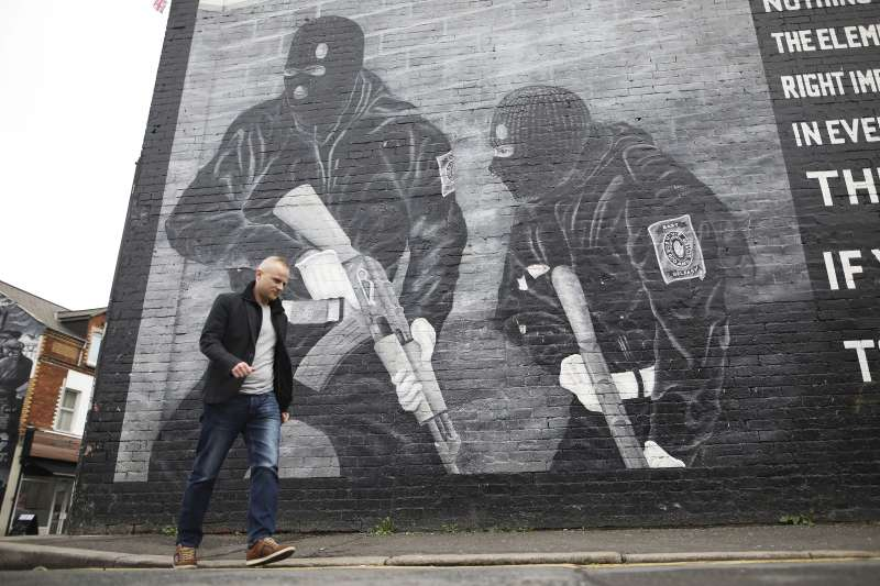 一名「阿爾斯特志願軍」忠誠支持者走過北愛爾蘭的塗鴉牆邊。(AP)