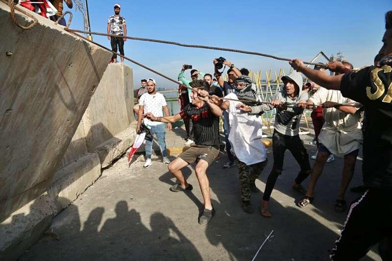 10月25日,伊拉克全國性反政府示威再起,巴格達解放廣場旁的民眾企圖翻倒路障。(AP)