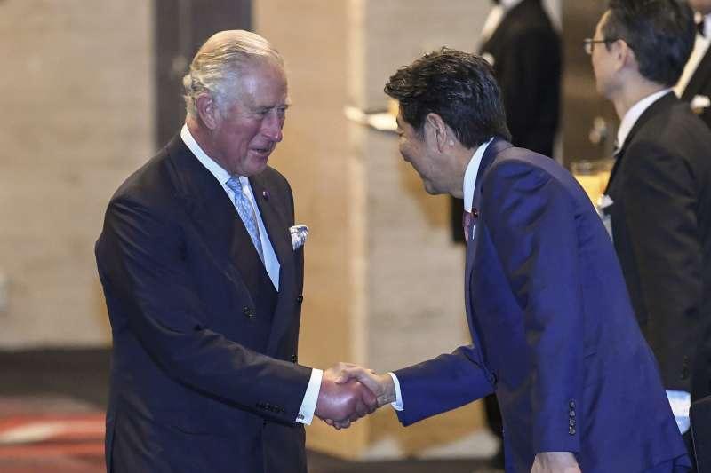 英國查爾斯王子參加日本德仁天皇登基儀式,與日本首相安倍晉三握手。(AP)