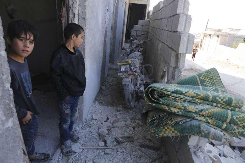 巴里沙的孩童與遭到美軍轟炸的廢墟。(美聯社)