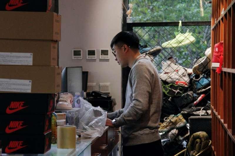 跟朋友一起經營運動鞋商店的管添在檢查庫存。 圖片來源:RAFFAELE HUANG/THE WALL STREET JOURNAL