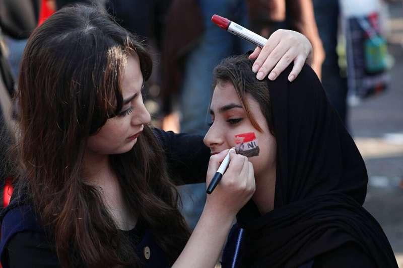 一名反政府的伊拉克抗議者在同伴的臉上彩繪伊拉克國旗。(美聯社)