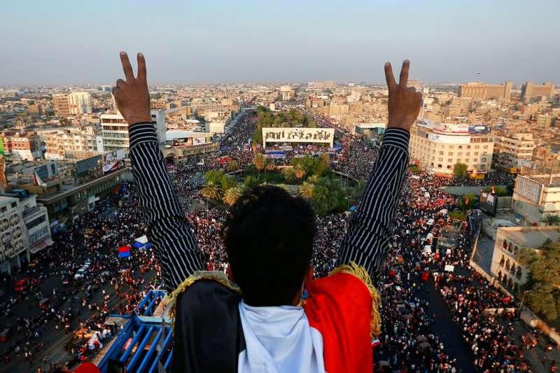 一名伊拉克示威者對著巴格達解放廣場的人群比出勝利手勢。(美聯社)