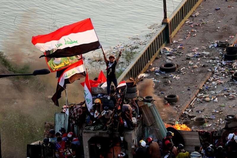 在巴格達街頭揮舞伊拉克國旗的抗議者。(美聯社)