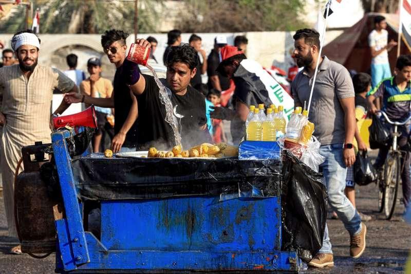 一名為抗議者準備免費食物的伊拉克小販。(美聯社)