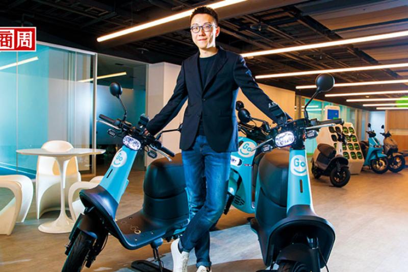 GoShare新事業總監姜家煒坐在自家製造機車上,認為有自有硬體製造及電源交換系統,才能掌握消費者的全程體驗。(攝影者.郭涵羚)