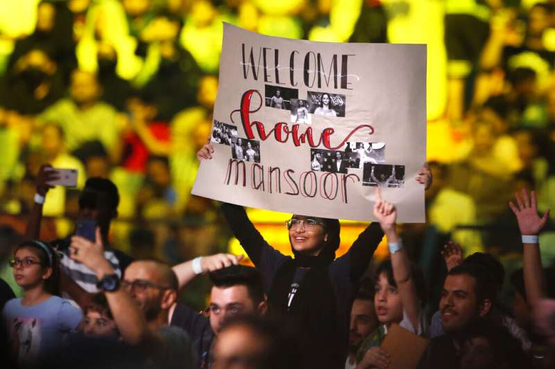WWE第一位沙國選手曼索爾出賽時現場觀眾舉海報加油。(美聯社)