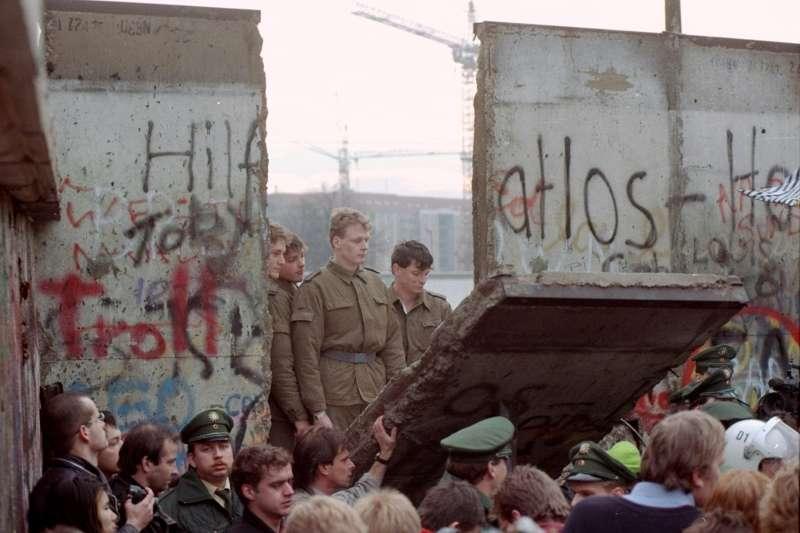 1989年11月13日,東德邊境守衛駐守在倒塌的柏林圍牆前。(AP)