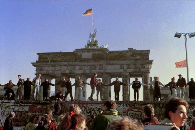 1989年11月,民眾爬上布蘭登堡門前的柏林圍牆,歡欣鼓舞地慶祝圍牆倒塌。(AP)