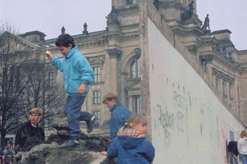 1990年,東西德正式統一,孩童在柏林圍牆的殘跡上玩耍。(資料照,AP)