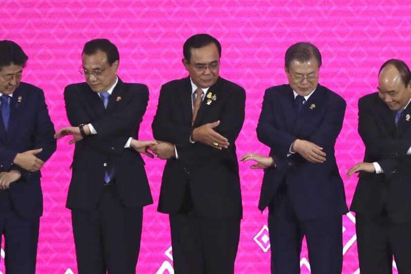 東協峰會3日在泰國登場,(左起)日相安倍、中國總理李克強、泰國總理帕拉育、南韓總統文在寅、越南總理阮春福正在準備握手合照。(美聯社)