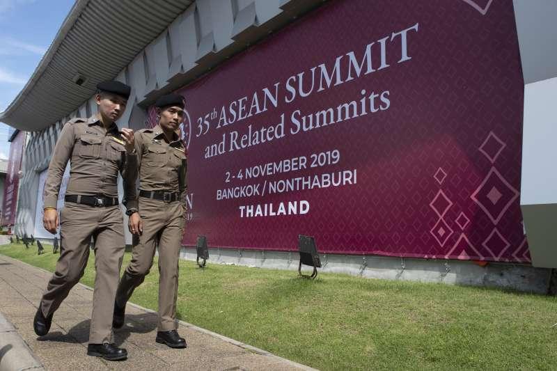 第14屆東亞峰會及第35屆東協峰會在泰國舉行,圖為泰國警察走過活動宣傳看板(AP)