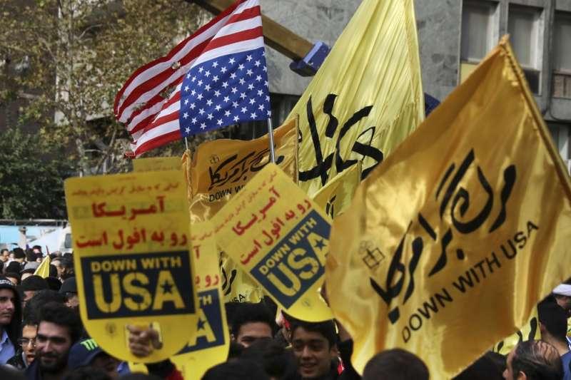 伊朗民眾聚集在前美國大使館前方,倒掛美國國旗並高舉「美國倒台」等標語,紀念人質危機40周年。(AP)