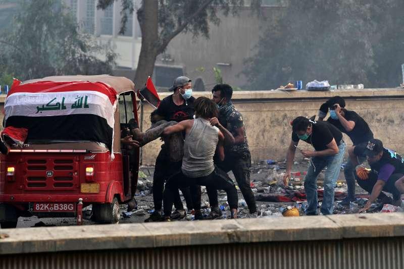 伊拉克反政府示威潮,一群人正把受傷同伴抬上嘟嘟車(Tuk Tuk)以便送往醫院。(AP)