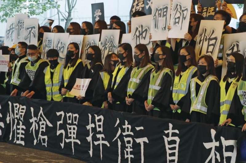 香港中文大學畢業生在2019年11月7日的畢業典禮上戴口罩手舉標語橫幅抗議。(美聯社)