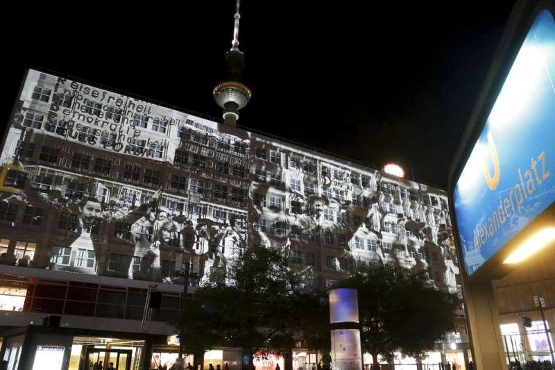 正值柏林圍牆倒塌30周年, 德國柏林亞歷山大廣場投放1989年東德人民抗議的影片。(AP)