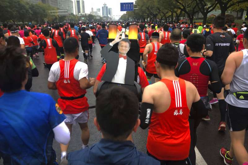 北京馬拉松一位參賽者背著阿里巴巴創辦人馬雲的肖像起跑。(美聯社)