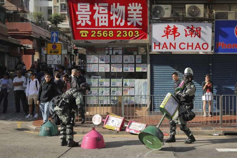 香港警察在街頭清除抗爭者不下的路障。(美聯社)