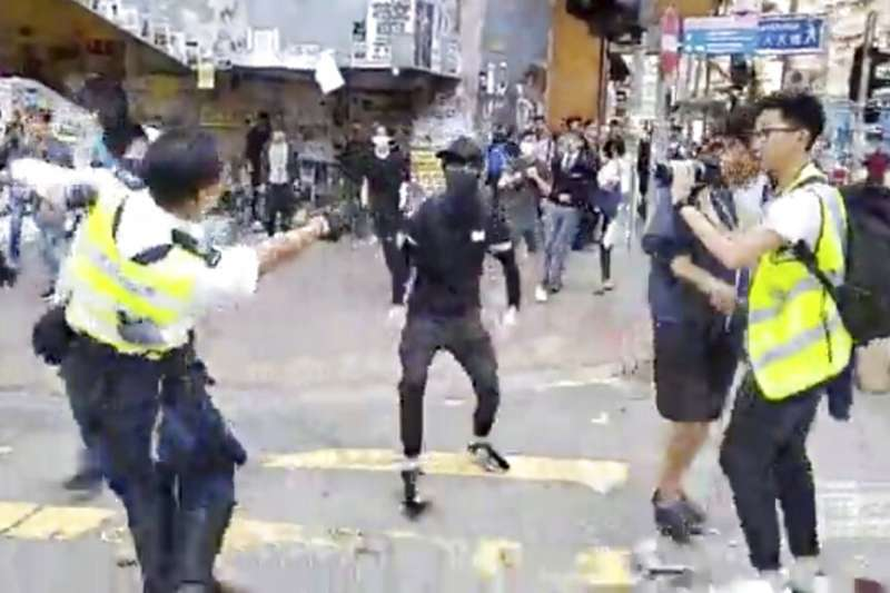 一名香港交通警察開槍射擊黑衣蒙面的抗爭者。(美聯社)