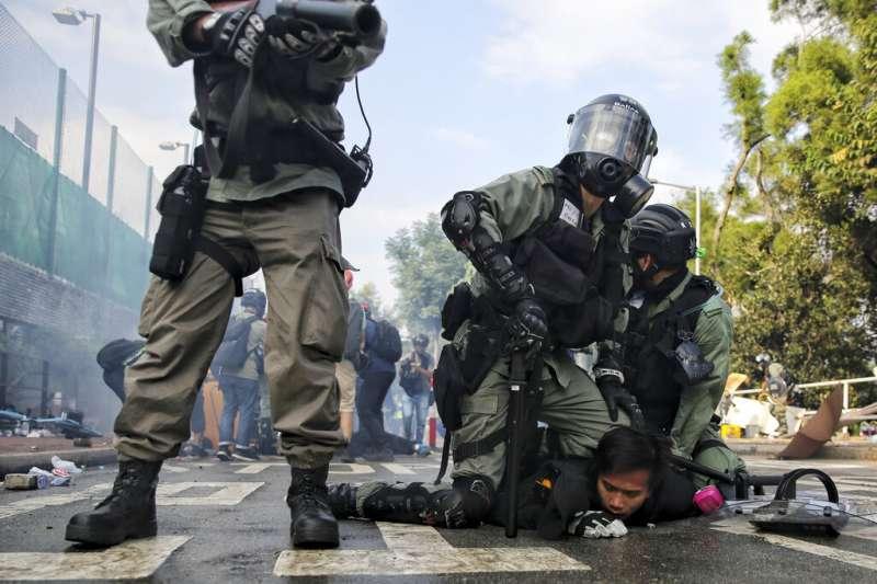12日,在警民衝突最嚴重的香港中文大學校園,警方壓制一名學生。(AP)