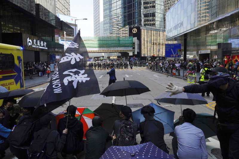 香港「反送中」抗爭者(持雨傘的群眾)11日在街頭與警察對峙。(美聯社)
