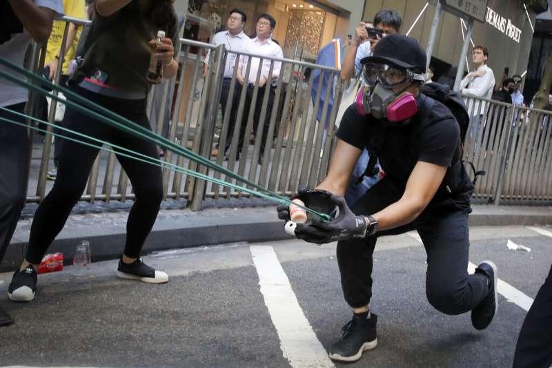 香港抗爭者11日以彈弓發射石塊。(美聯社)