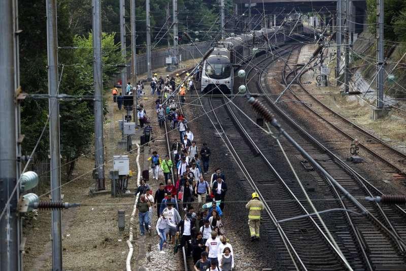 由於列車電纜遭到干擾、鐵軌附近也被投擲雜物,香港列車被迫停駛,乘客只能徒步走到車站。(美聯社)