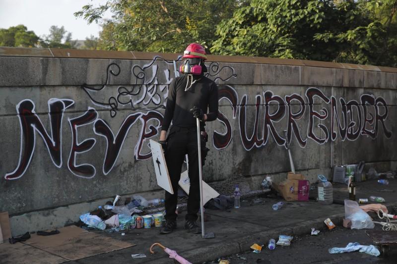香港中文大學學生11月12日與警方爆發衝突,圖為學生站在「二號橋」衝突現場,背後塗鴉寫:永不投降。(AP)