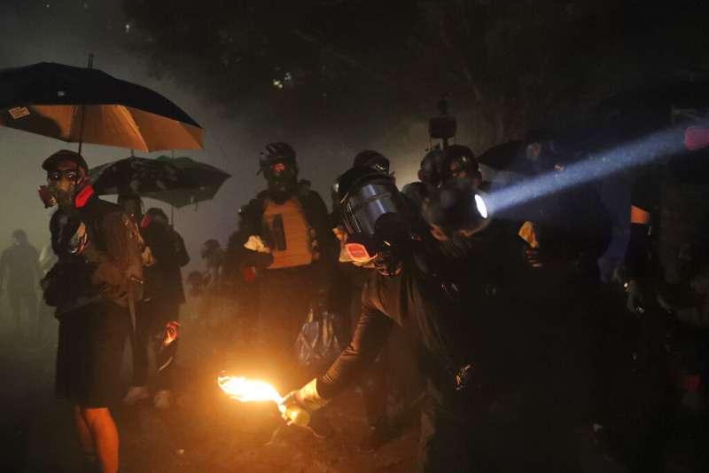 抗爭學生12日在中文大學以汽油彈跟路障對抗試圖衝進校園的香港警察。(美聯社)