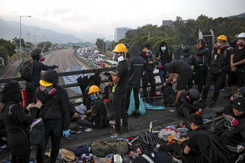 香港三罷抗爭越演越烈,多間大學遭到防暴警闖入發射催淚子彈,以中文大學的衝突最為嚴重。圖為抗爭學生13日一早就在中文大學的二號橋,準備抵禦隨時可能攻進校園的香港警察。(美聯社)