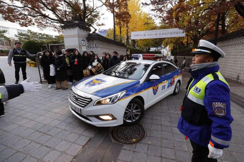 南韓14日舉行大學修學能力試驗,警察忙著把遲到或者忘了帶證件的考生送往考場。(美聯社)